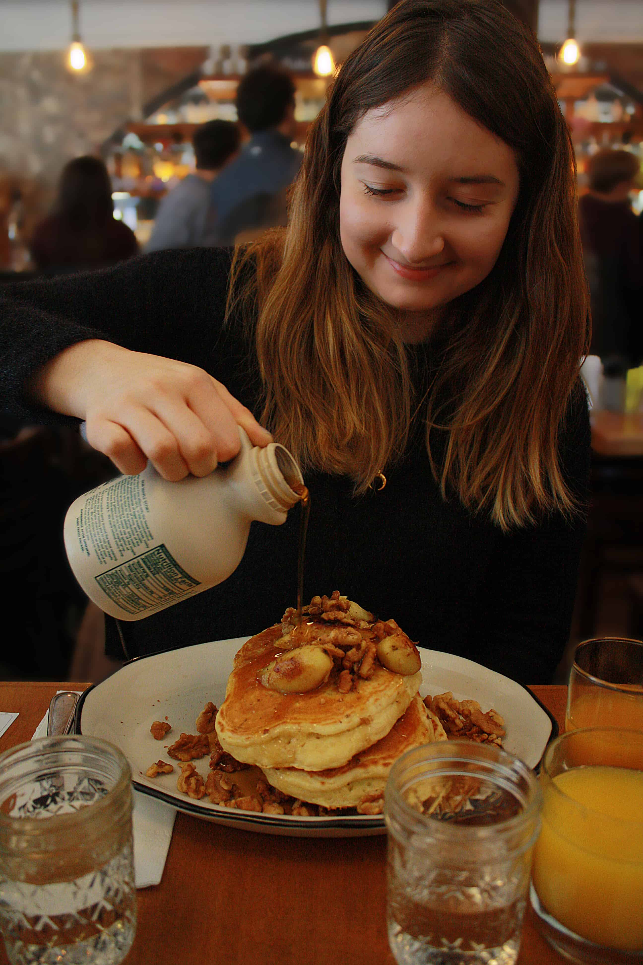 pouring maple syrup on pancakes at Bubby's, NYC