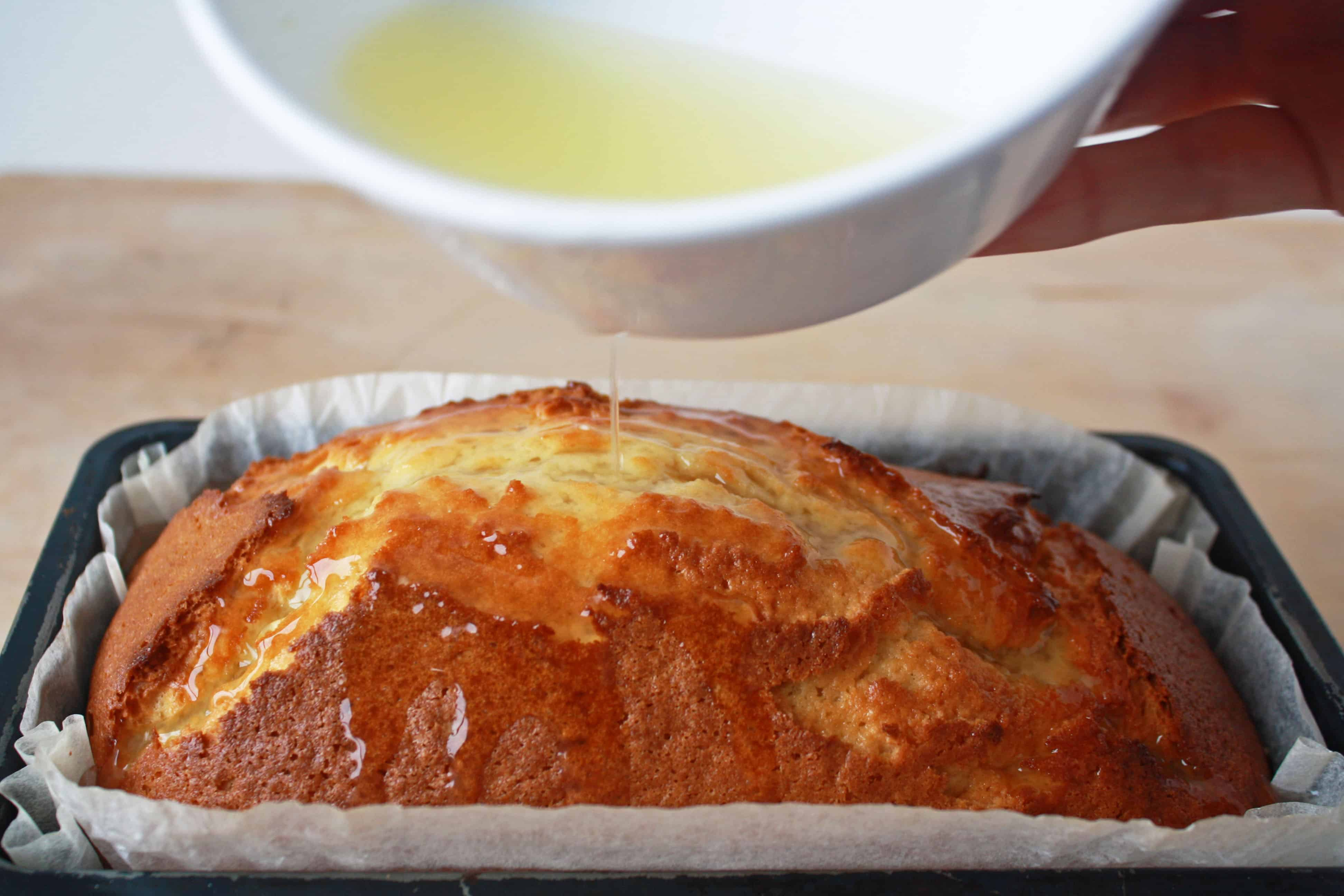 Drizzling lemon juice over lemon loaf cake