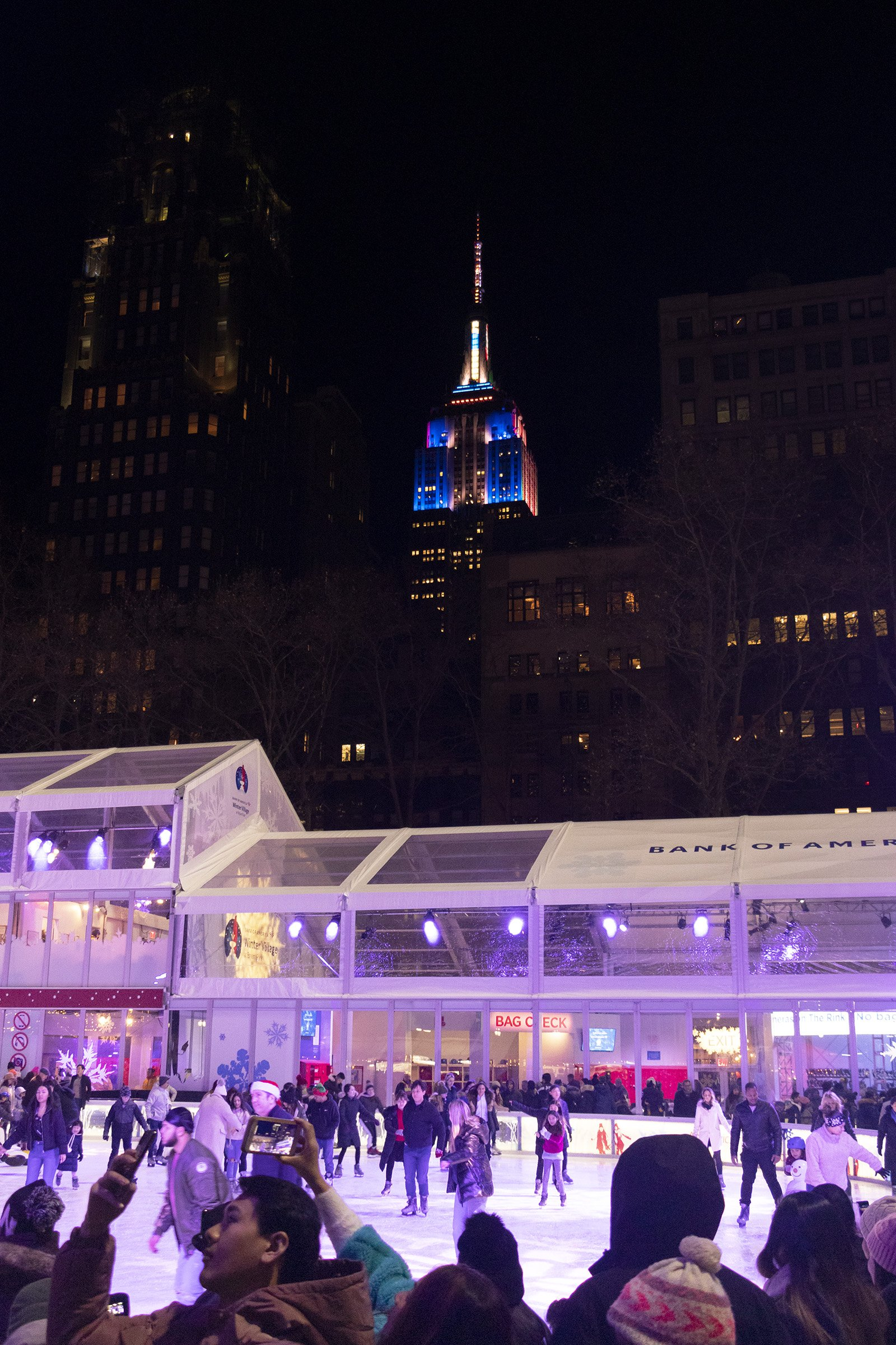 Bryant Park skating rink and Empire State Building with Christmas lights