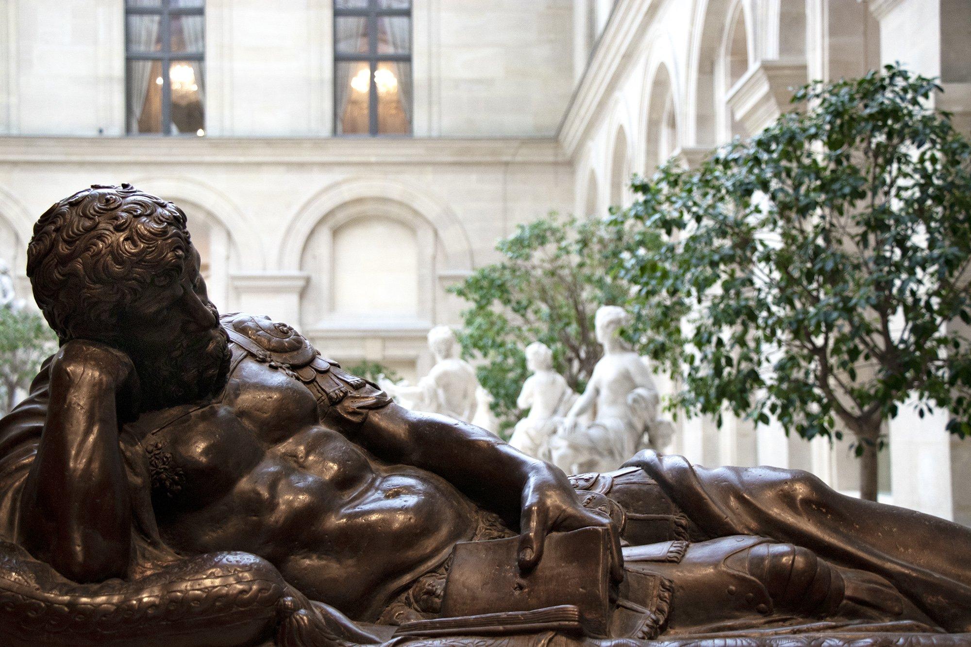 Statue of man reading book in Louvre, Paris